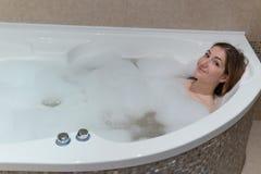 Mujer linda que se relaja en el cuarto de baño fotografía de archivo libre de regalías