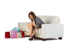 Mujer linda que se sienta en el sofá que saca sus zapatos Foto de archivo
