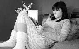 Mujer linda que se sienta en la cama que se relaja mirando la red social en la tableta blanco y negro foto de archivo libre de regalías