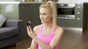 Mujer linda que se sienta en la estera de la yoga y el tel?fono m?vil de la ojeada para las canciones metrajes