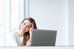 Mujer linda que se sienta en la tabla con el ordenador portátil Imagenes de archivo