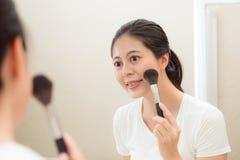 Mujer linda que sostiene el cepillo del maquillaje usando los cosméticos Imagenes de archivo