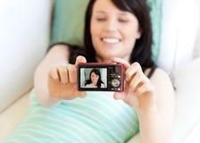 Mujer linda que toma el cuadro de se que miente en cama Imagen de archivo