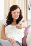 Mujer linda que ve la TV el mirar en la cámara Foto de archivo libre de regalías