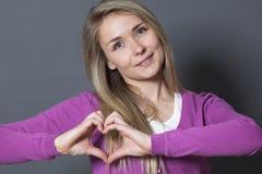 Mujer linda 20s que muestra forma del corazón con las manos Imagen de archivo