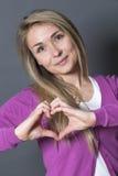 Mujer linda 20s que muestra forma del corazón con las manos Foto de archivo