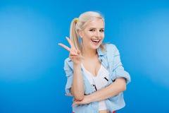 Mujer linda sonriente que muestra el signo de la paz Imagen de archivo libre de regalías