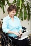 Mujer lisiada con la computadora portátil Foto de archivo