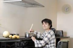 Mujer lisiada en sillón de ruedas que cocina la cena Fotos de archivo libres de regalías