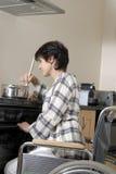 Mujer lisiada en sillón de ruedas que cocina la cena Imágenes de archivo libres de regalías