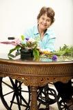 Mujer lisiada que arregla las flores Imagen de archivo