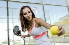 Mujer lista para el servicio del tenis de la paleta Foto de archivo