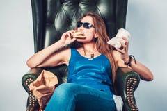 Mujer loca divertida que come la comida basura de la hamburguesa y Fotos de archivo libres de regalías