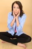 Mujer loca joven que se sienta en el piso que tira de la expresión facial tonta Foto de archivo libre de regalías