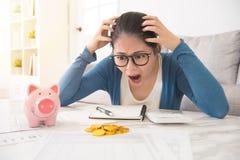 Mujer loca ver el dinero de la hucha Fotos de archivo