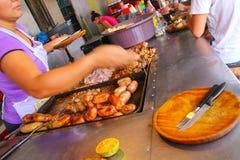 Mujer local que cocina la carne para el asado en Mercado 4 en Asuncion, par Imagenes de archivo