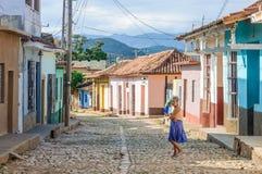 Mujer local y casas coloridas en Trinidad, Cuba Imágenes de archivo libres de regalías
