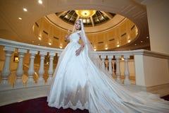 Mujer lujosa hermosa joven en el vestido de boda que presenta en interior lujoso Novia con el vestido de boda enorme en señorío m Foto de archivo