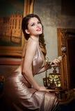 Mujer lujosa hermosa joven en vestido elegante que sonríe sosteniendo un teléfono del vintage. Mujer joven hermosa en paisaje clás Foto de archivo