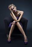 Mujer lujosa hermosa que se sienta en silla foto de archivo libre de regalías