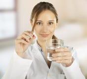 Mujer médica que toma una píldora fotos de archivo