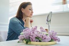 Mujer madura 40 a?os que miran su cara en el espejo, sentada femenina en la tabla en casa que hace maquillaje fotografía de archivo libre de regalías