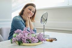 Mujer madura 40 a?os que miran su cara en el espejo, sentada femenina en la tabla en casa que hace maquillaje imagen de archivo