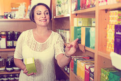 Mujer madura alegre en tienda Foto de archivo