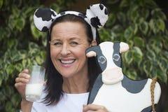 Mujer madura amistosa con la llorica y la vaca Imagen de archivo libre de regalías