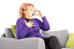 Mujer madura asentada en un sofá que toma el tratamiento del asma con inhal Imágenes de archivo libres de regalías