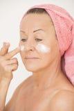 Mujer madura atractiva con la nata en cara Imágenes de archivo libres de regalías