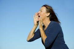 Mujer madura atractiva que grita hacia fuera ruidosamente Fotografía de archivo