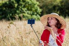 Mujer madura atractiva que hace un autorretrato atractivo en el teléfono móvil Imagen de archivo