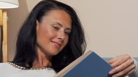 Mujer madura atractiva que sonríe alegre leyendo el libro interesante almacen de metraje de vídeo