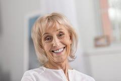 Mujer madura blanda que sonríe en la cámara foto de archivo libre de regalías