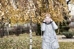 Mujer madura cerca del abedul del otoño Foto de archivo