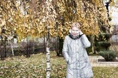 Mujer madura cerca del abedul del otoño Fotos de archivo libres de regalías
