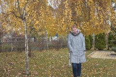 Mujer madura cerca del abedul del otoño Fotografía de archivo