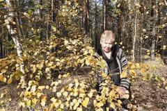 Mujer madura cerca del abedul del otoño Fotos de archivo