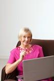 Mujer madura con el ordenador Foto de archivo libre de regalías