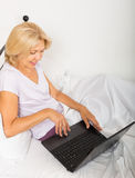 Mujer madura con el ordenador portátil en cama Imagen de archivo libre de regalías