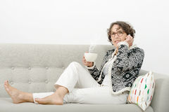 Mujer madura con el teléfono, té de consumición Imagen de archivo