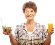 Mujer madura con la ensalada y el jugo imagenes de archivo