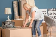 Mujer madura con las cajas y las pertenencia móviles en el nuevo hogar fotografía de archivo