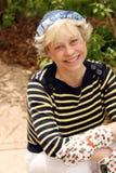 Mujer madura con los guantes que cultivan un huerto Imagen de archivo libre de regalías