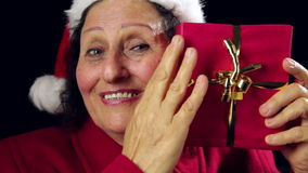 Mujer madura con Santa Cap Caressing un regalo rojo almacen de metraje de vídeo