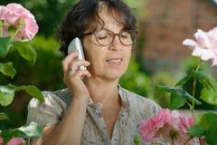 Mujer madura con un teléfono en su jardín Foto de archivo