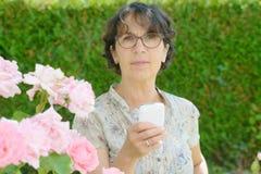Mujer madura con un teléfono en su jardín Fotos de archivo libres de regalías