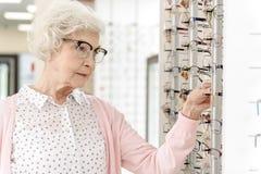 Mujer madura concentrada en tienda óptica Imágenes de archivo libres de regalías