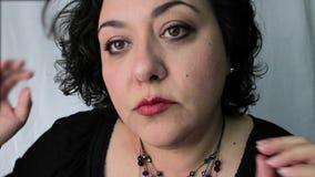 Mujer madura de Latina que ajusta el pendiente y el pelo almacen de metraje de vídeo